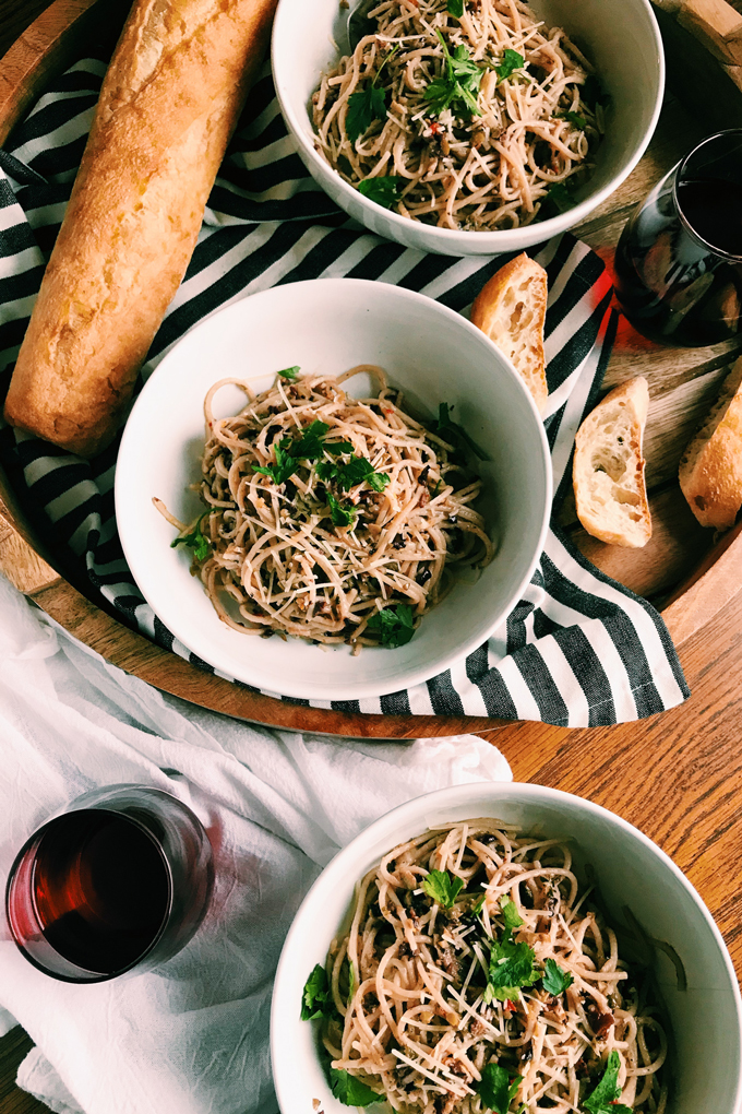 Pasta with Olive Tapenade, parmesan, parsley in white bowls, red wine, baguette, striped towel