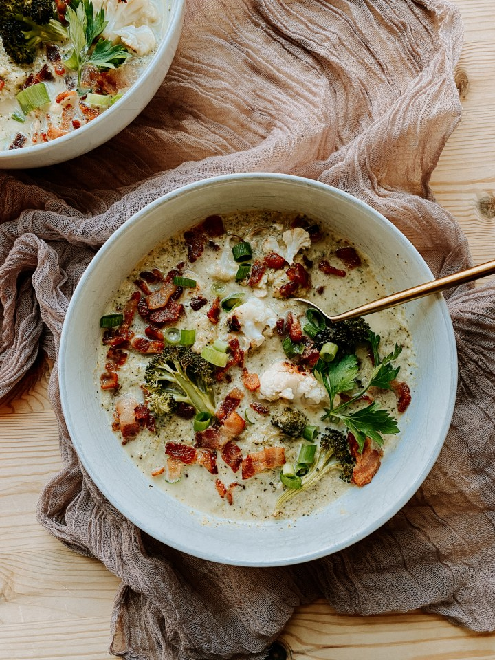 a gold spoon resting in a white bowl filled with Roasted Broccoli Cauliflower Soup
