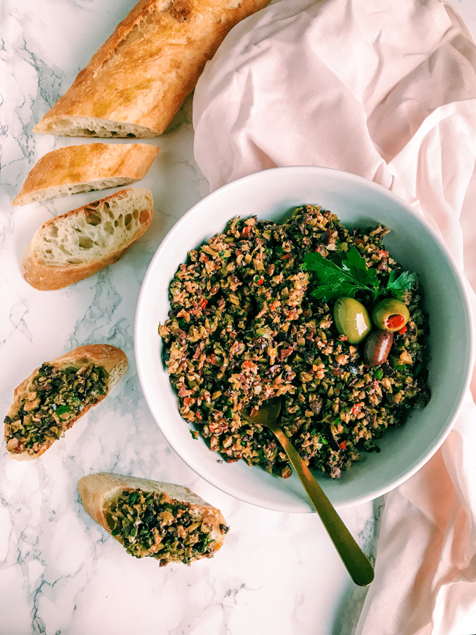 Olive Tapenade in a white bowl with a baguette and bread slices, pink towel