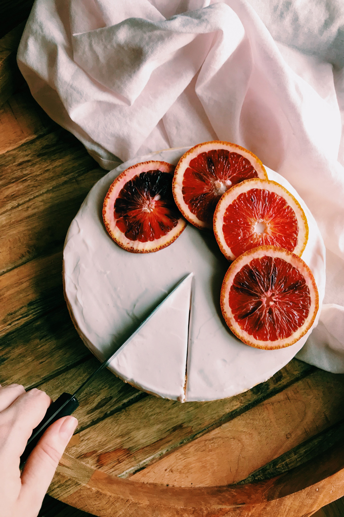 slicing into a cheesecake with blood orange slices on top
