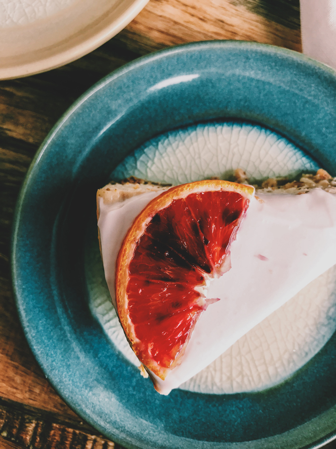 closeup of cheesecake with blood orange slice on a teal plate