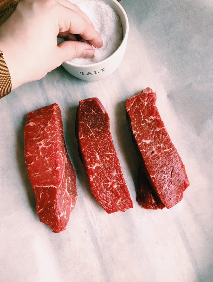 a hand dipping into a salt cellar next to three pieces of beef