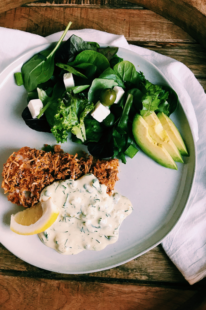 Crispy Oven Fried Fish and salad with avocado on a white plate