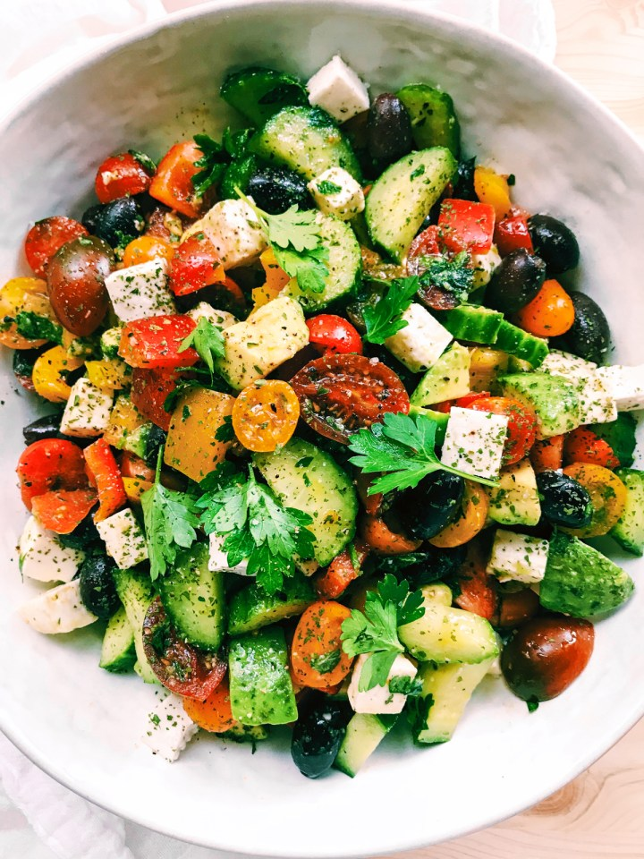 closeup of Crunchy Greek Salad with Avocado and Feta and herbs