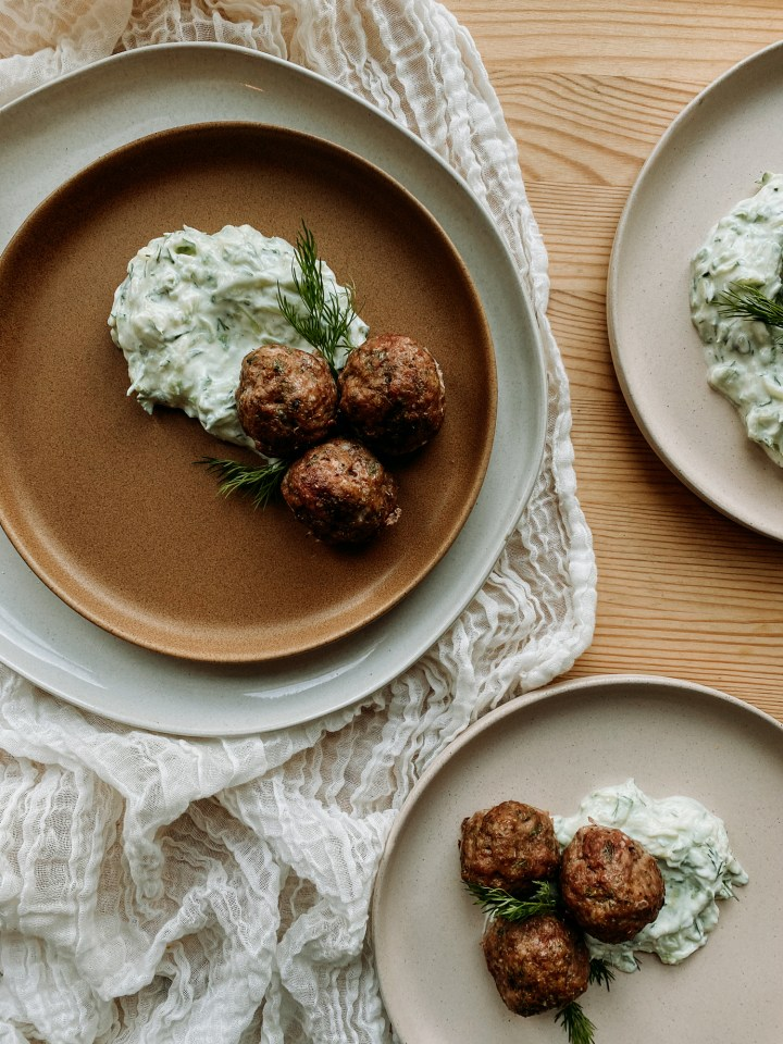 three plates on a wooden surface containing Greek Lamb Meatballs with Tzatziki Sauce