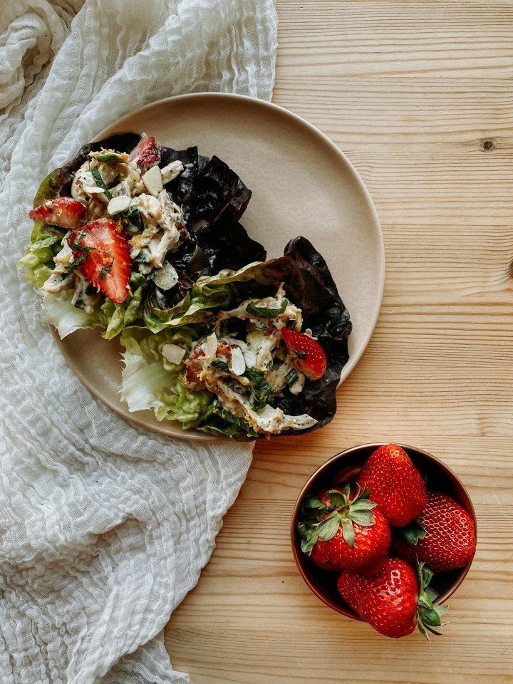 a bowl of strawberries next to a plate with a Strawberry Poppy Seed Chicken Salad filled butter lettuce cup