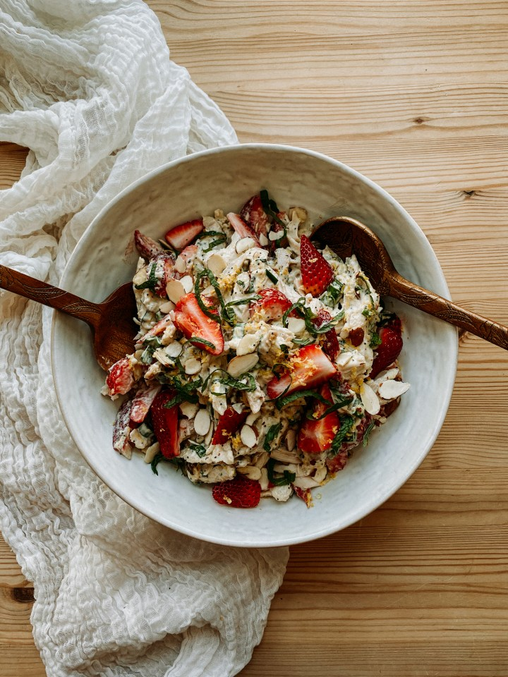 two wooden serving utensils in a white bowl of Strawberry Poppy Seed Chicken Salad on a white cloth lined wooden surface