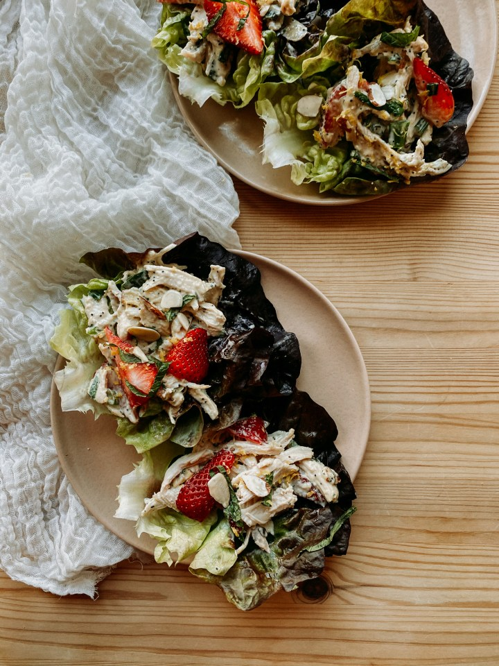 lettuce cups filled with Strawberry Poppy Seed Chicken Salad on two brown plates resting on a wooden surface