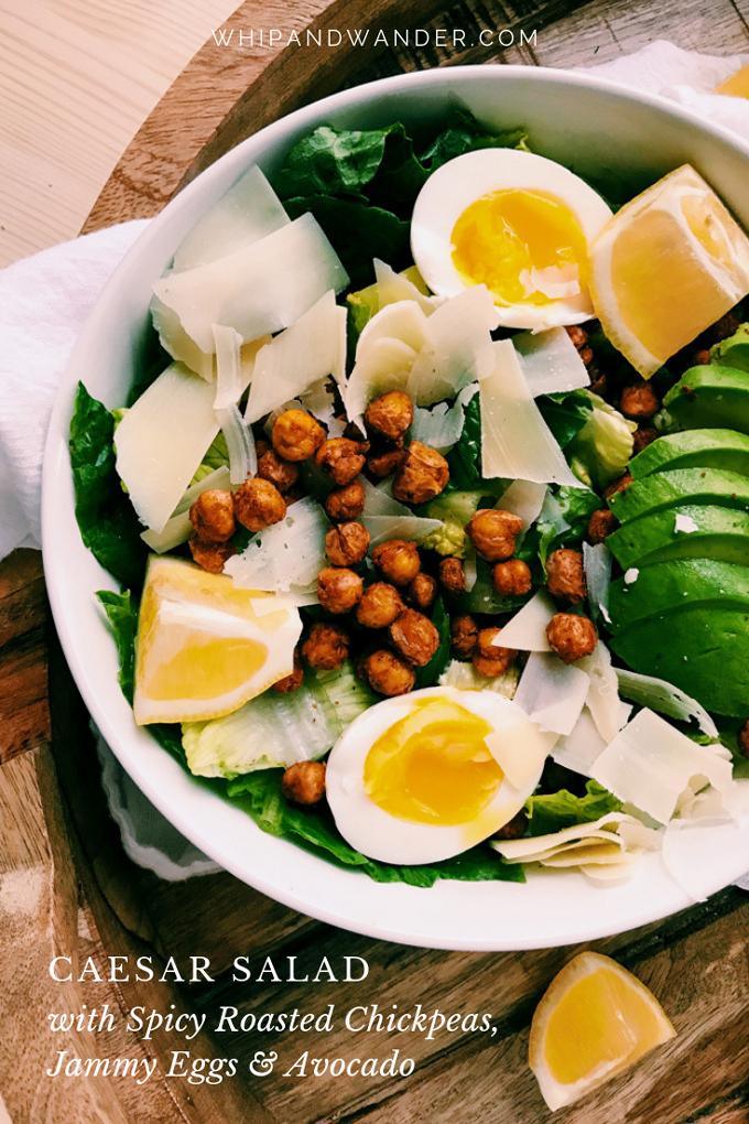 white salad bowl with eggs, avocado, lemon, parmesan, chickpeas, and salad greens