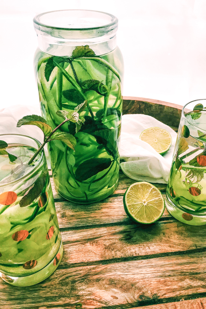 a glass pitcher fill of cucumber mint lime water, with two glasses of it