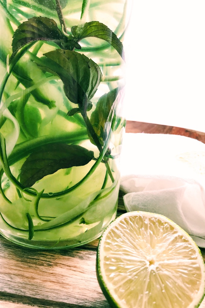 glass container with cucumber mint lime water with a sliced lime