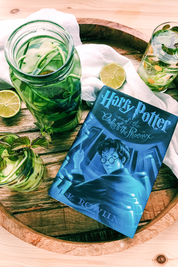 harry potter book next to a glass container of cucumber lime mint water