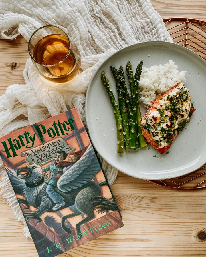 a harry potter book resting nex tto a plate with roasted salmon, asparagus, and rice and a glass of white wine