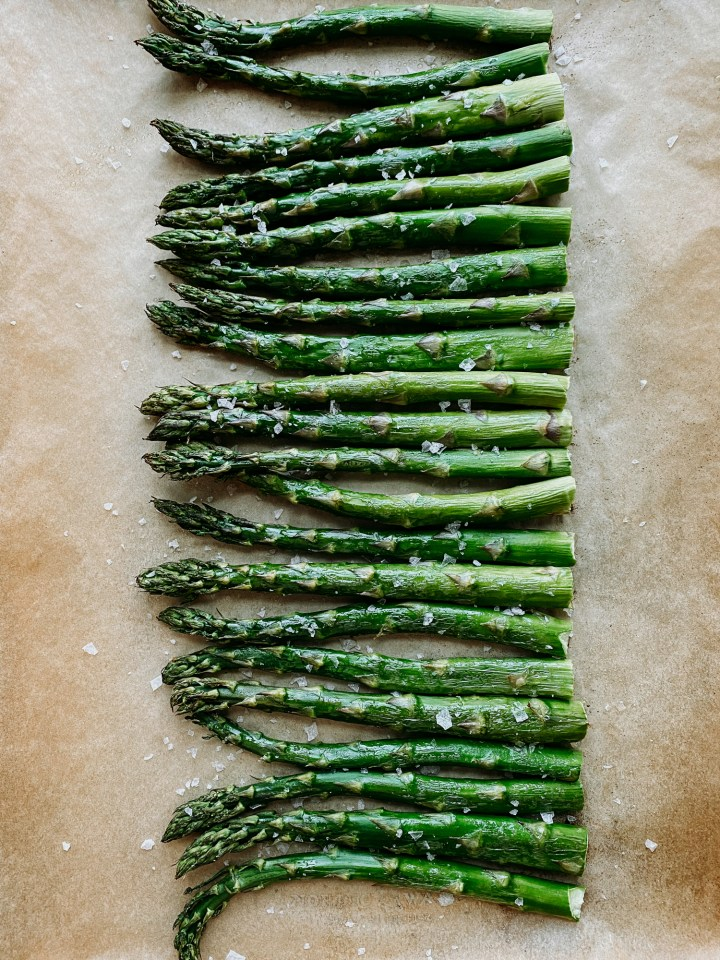 a row of broiled asparagus stalks on a parchment paper lined sheet pan