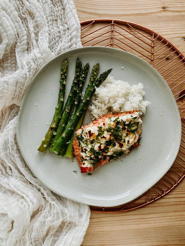 a white plate topped with a piece of salmon topped with feta, butter, and herbs, a pile of white rice, and several stalks of asparagus resting on a white cloth