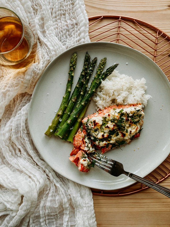a fork cutting into Petunia Dursley's Roasted Salmon with Feta and Herbs with asparagus and rice on a white plate, a glass of white wine is next to the plate