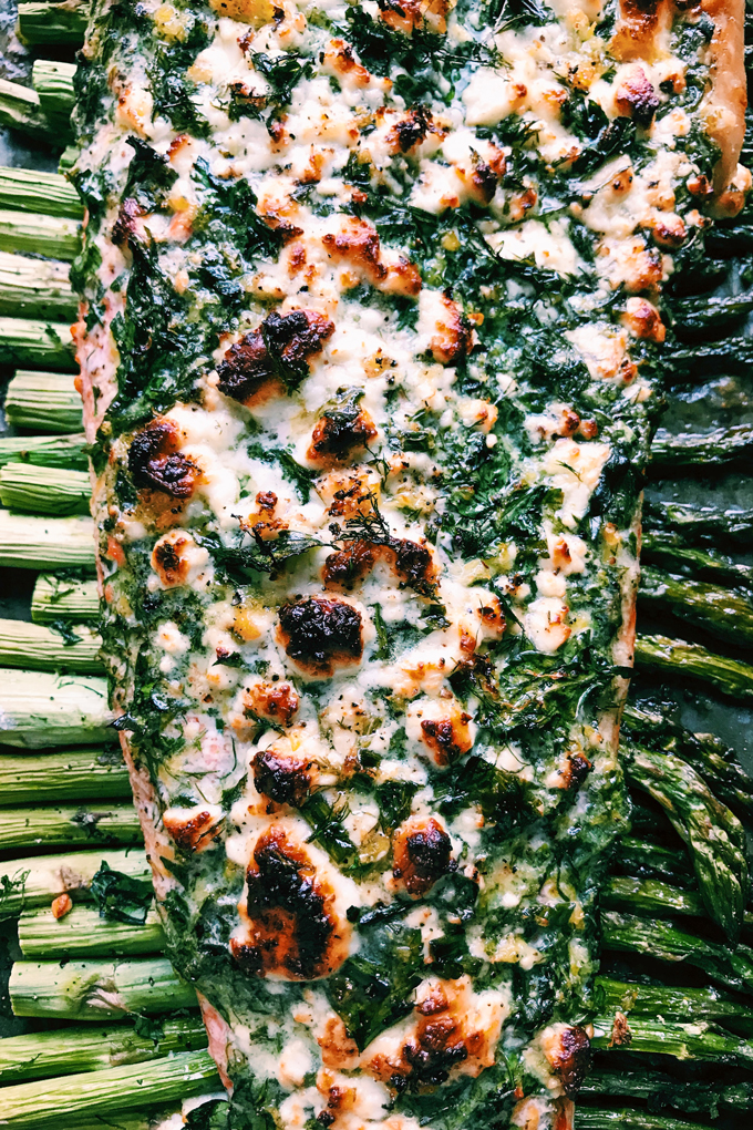 baked salmon with feta and herbs on asparagus on a baking sheet