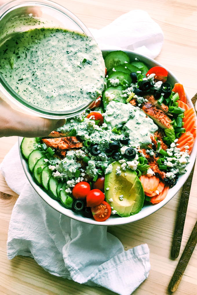 a hand pouring buttermilk jalapeno ranch dressing over a bowl of bbq chicken salad