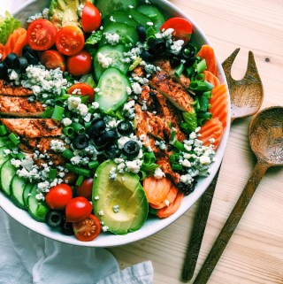 a white bowl with bbq chicken salad, cucumber, tomato, avocado slices and salad servers