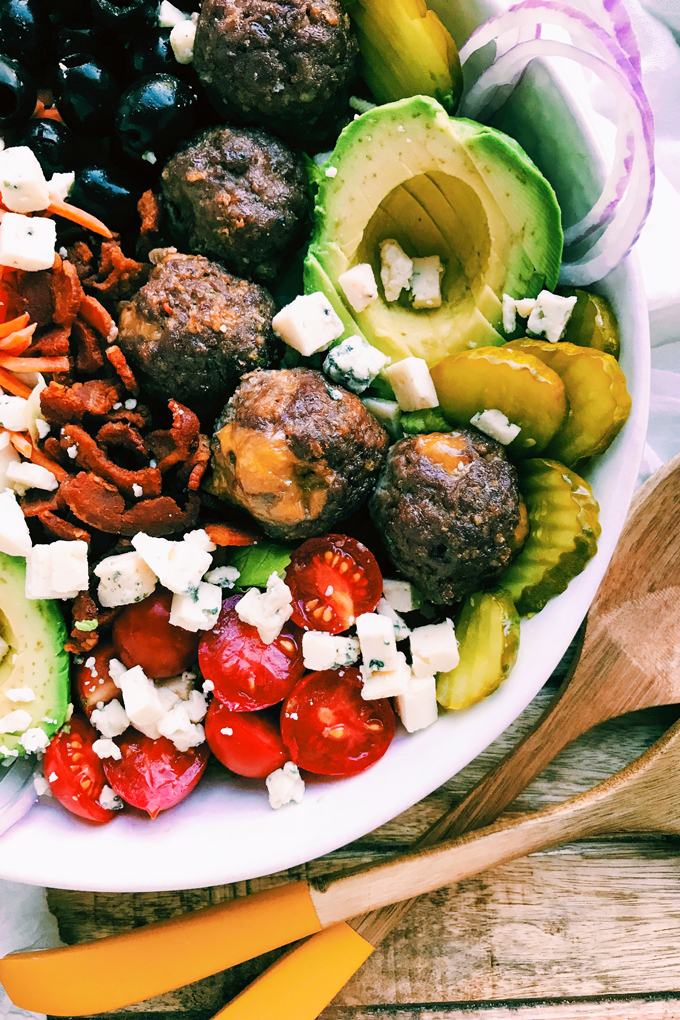 a closeup shot of cheese stuffed meatballs in a salad