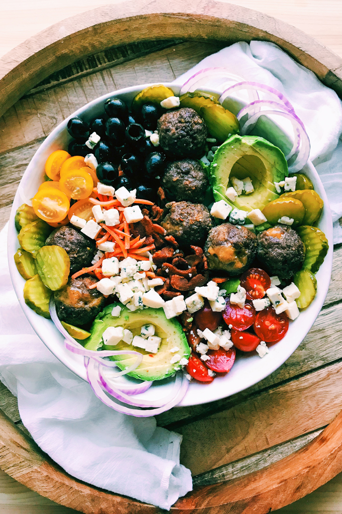 a burger salad with cheese stuffed meatballs, pickles, olives, bheese, tomatoes, avocado, pickles, carrots in a white bowl