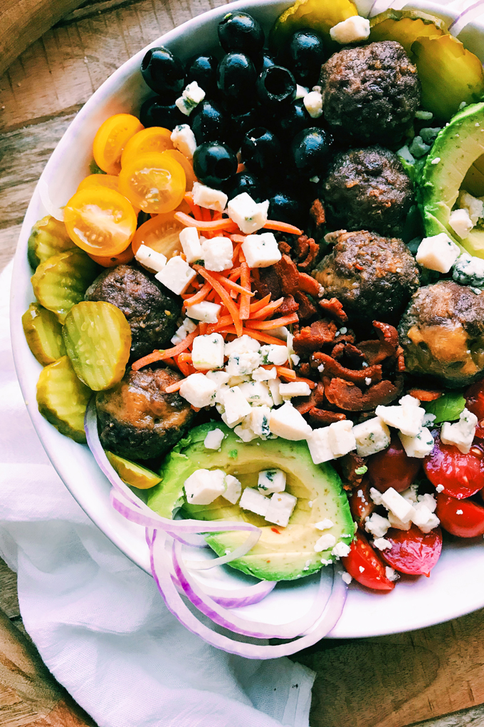 pickles, avocado, onion, tomato, cheese, and meatballs in a white salad bowl