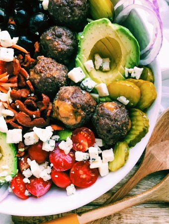 cheese stuffed meatballs over a vegetable salad in a white bowl
