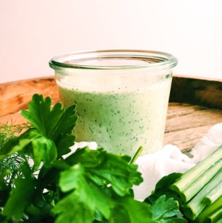 a glass jar of buttermilk jalapeno ranch dressing behind herbs on a wooden tray