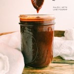 bbq sauce dripping from a gold spoon into a jar