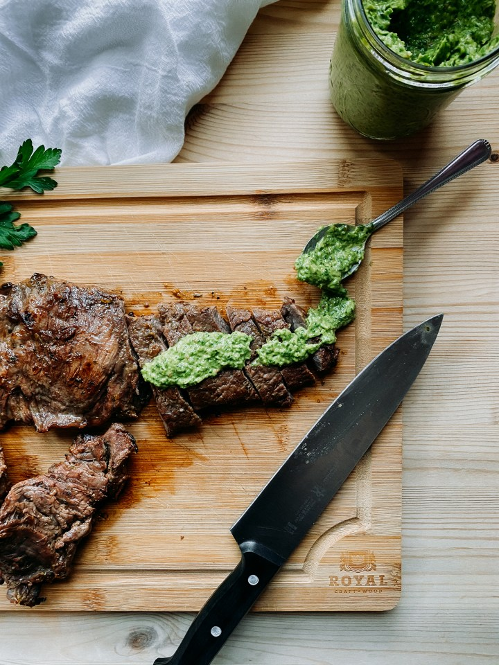 Grilled Skirt Steak slices with avocado chimichurri sauce on top on a wooden cutting boar with a spoonful of sauce and a knife resting nearby