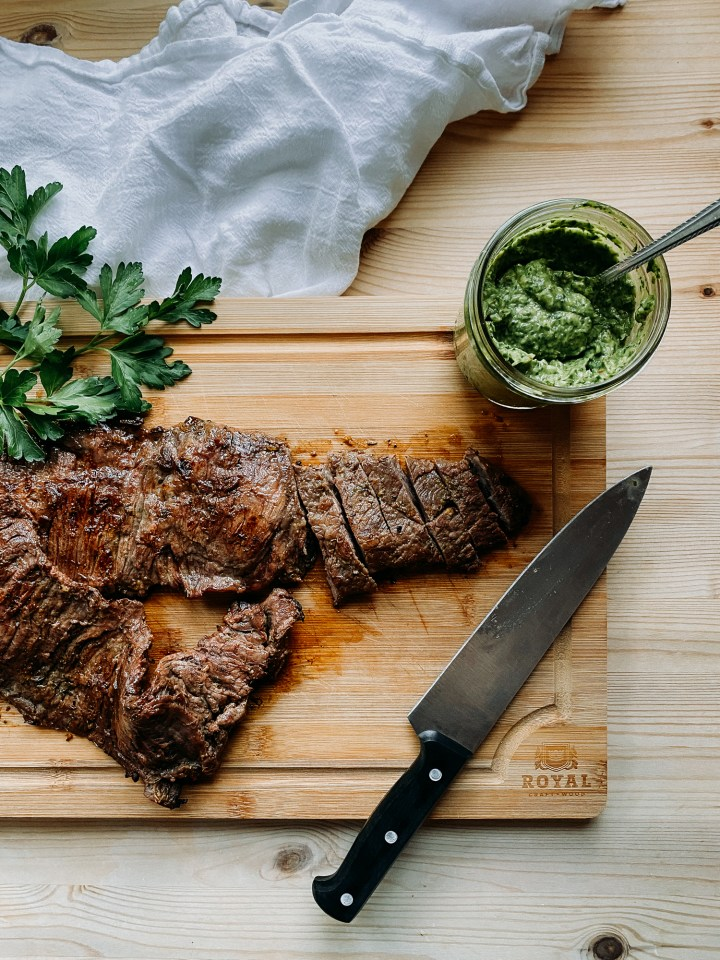 a wooden cutting board with grilled skirt steak, a knife, and a gladd jar of avocado chimichurri sauce