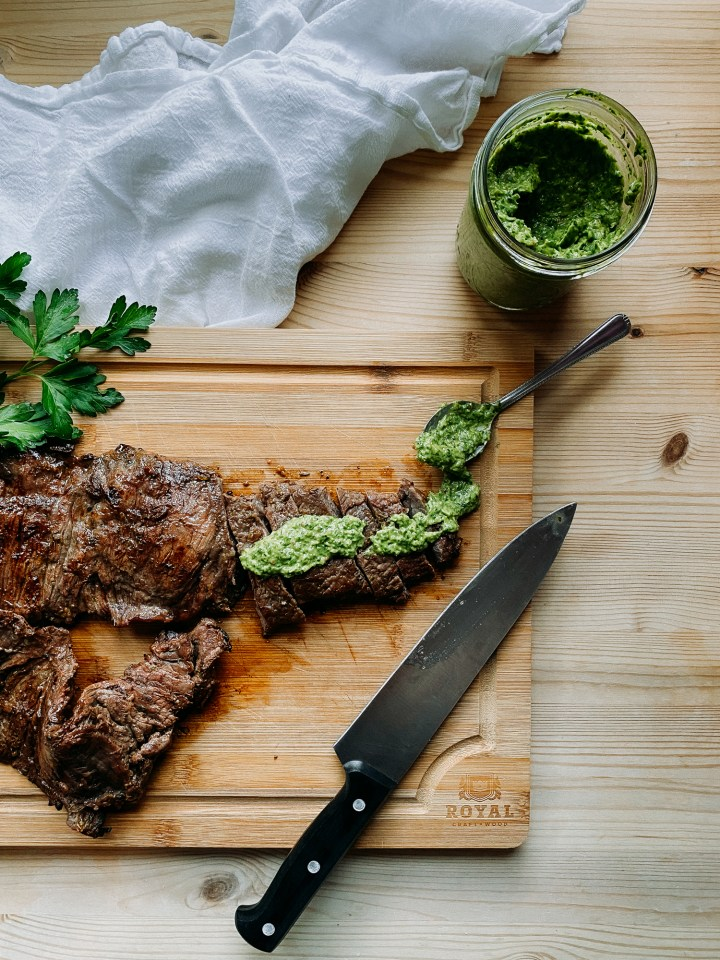 Grilled Skirt Steak with Avocado Chimichurri Sauce on a cutting board resting on a wood table with a white towel and a jar of green sauce