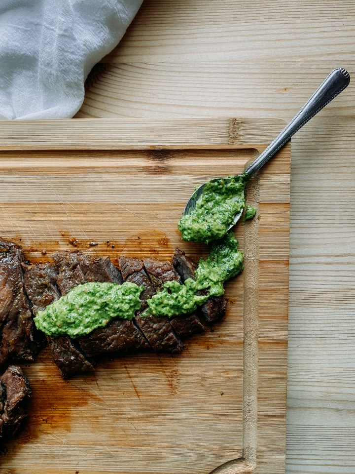 green avocado chimichurri sauc eon a spoon and on top of slices of grilled skirt steak on a wooden cutting board