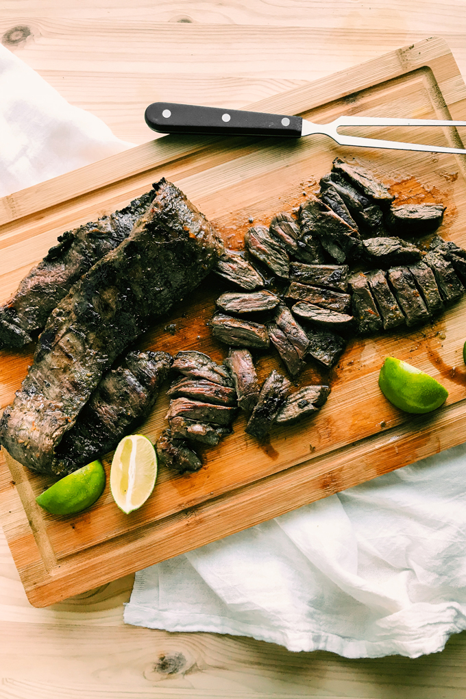 grilled skirt steak and limes on a bamboo cutting board
