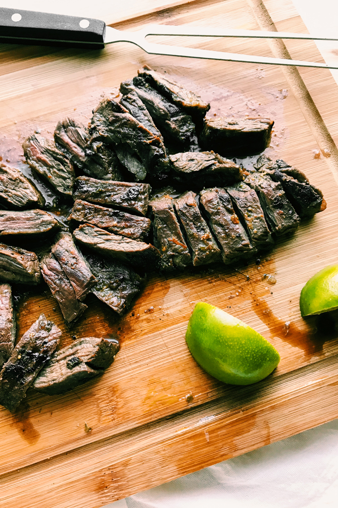 sliced grilled skirt steak and slices of lime ona bamboo cutting board