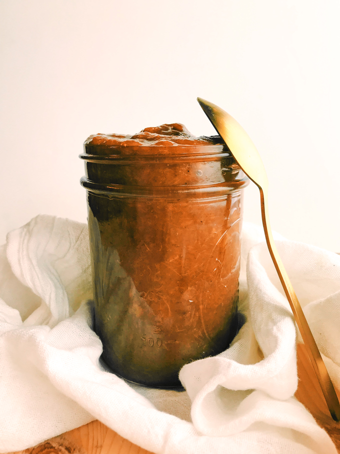 peach butter in a glass ball jar with a gold spoon and white towel