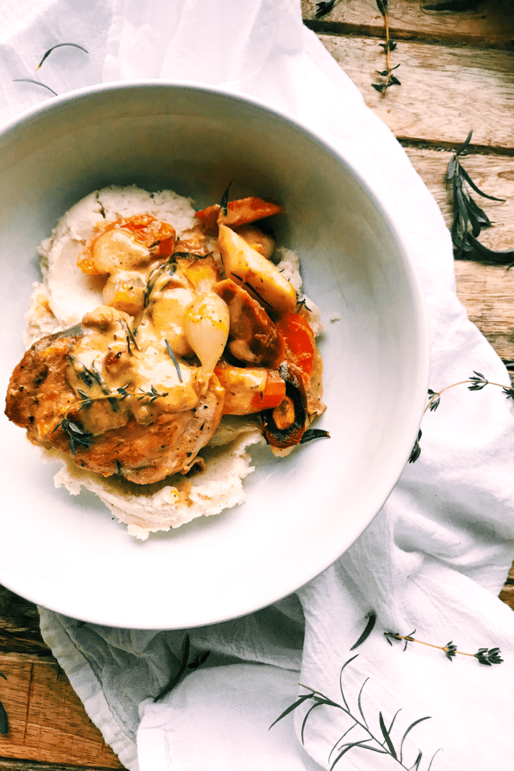 a white bowl with a chicken and vegetable dinner with orange dijon herb sauce