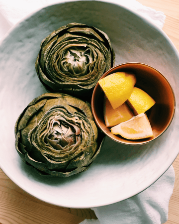 a white bowl with instant pot artichokes and lemon wedges in a copper dish