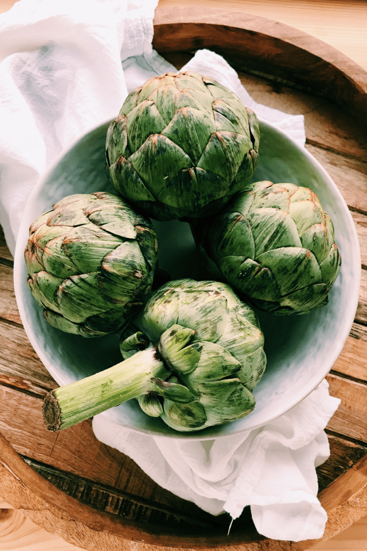 a white bowl filled with raw artichokes on a white towel