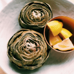 instant pot artichokes in a white dish with wedges of lemons in a copper bowl