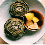pressure cooker artichokes in a white bowl with a copper bowl of lemon wedges