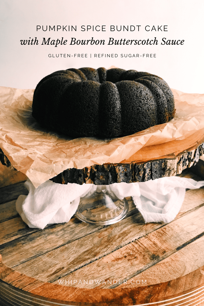 Pumpkin Spice Bundt Cake with Maple Bourbon Butterscotch Sauce on a wooden and glass cake stand with brown paper
