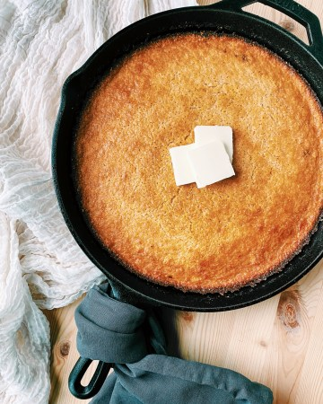 butter pats on top of a skillet cornbread resting on a white towel