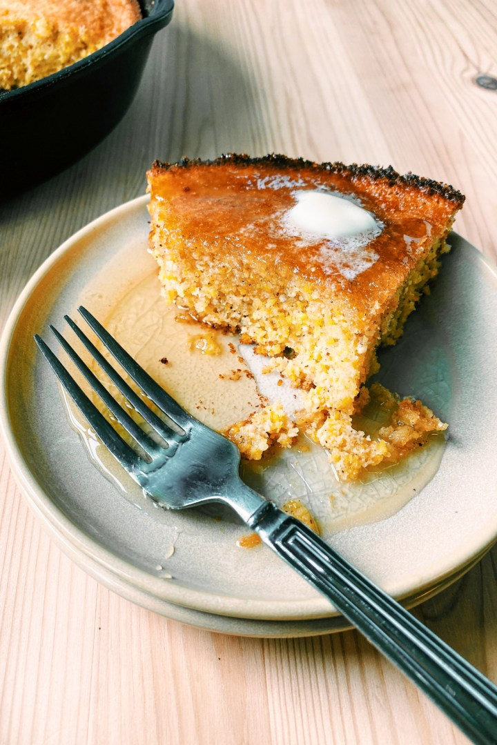 a plate of Brown Butter Buttermilk Skillet Cornbread partially eaten with butter and honey