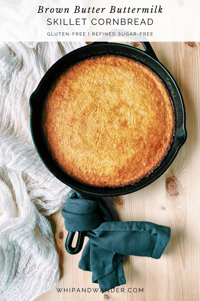 a cast iron skillet filled with Brown Butter Buttermilk Cornbread resting on a white towel with a gray towel wrapped around the handle