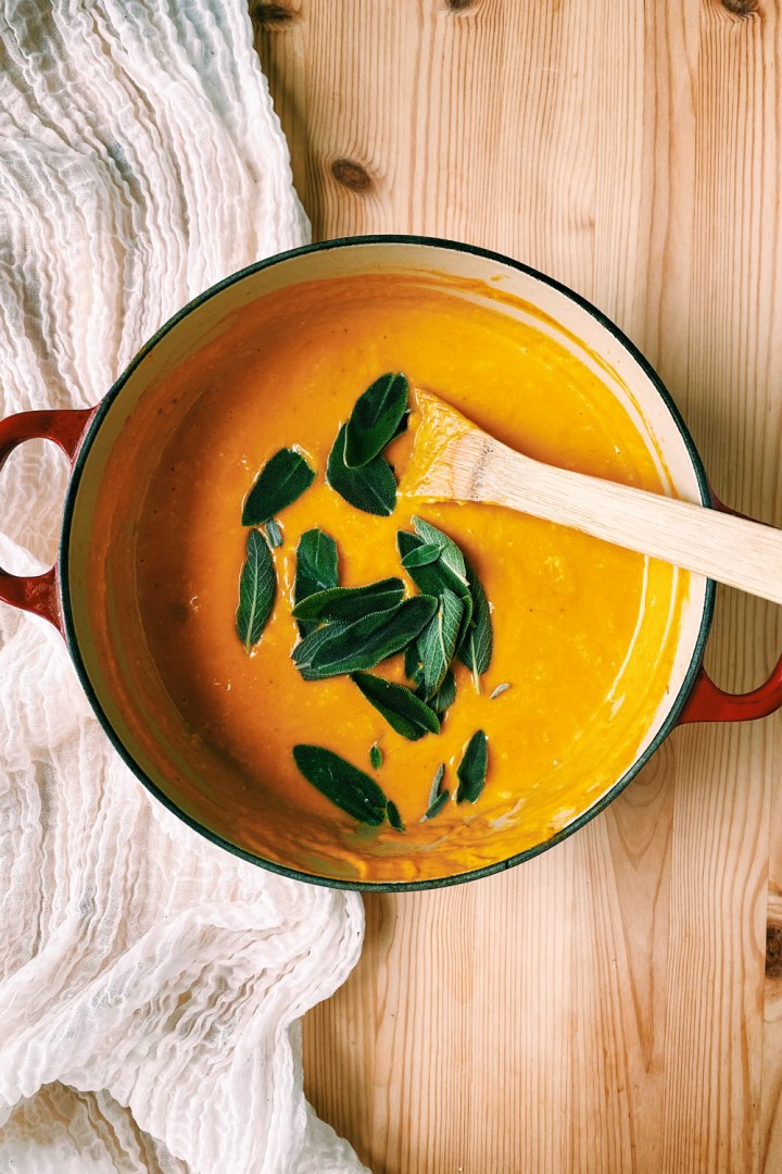a wooden spoon resting in a pot of butternut squash soup with fresh sage sprinkled on top