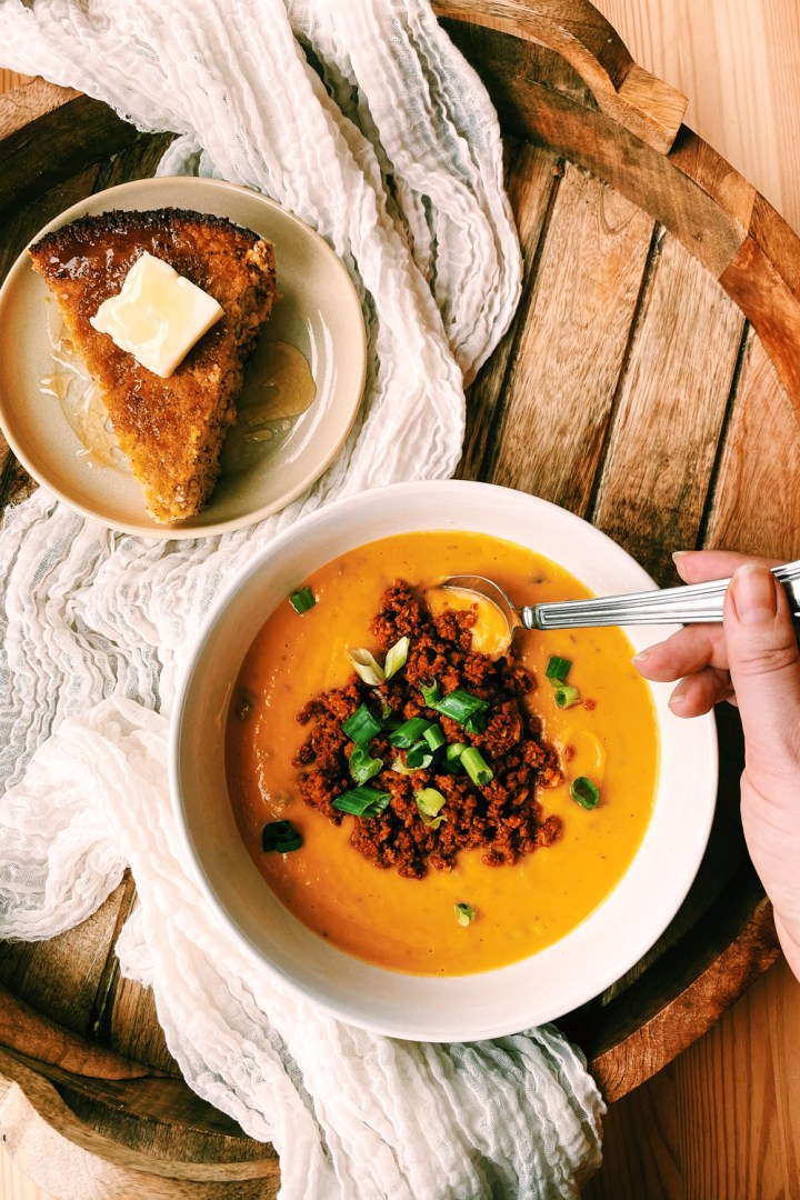 a hand spooning into a white bowl of butternut squash soup with spicy chorizo and green onions on top on a wooden tray with a slice of cornbread nearby