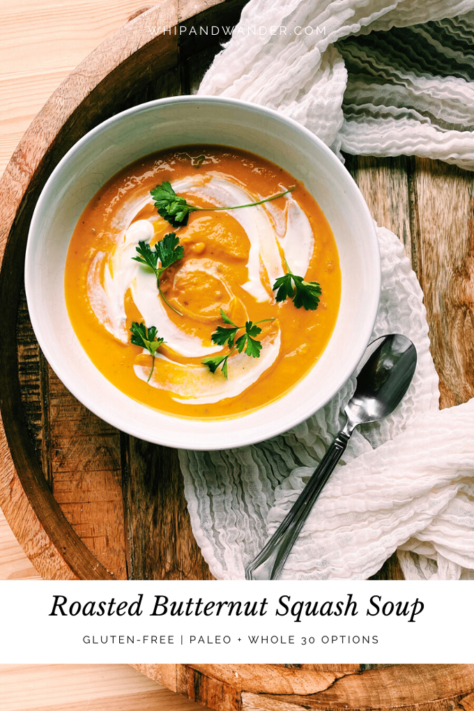 a wooden tray with a white bowl of Roasted Butternut Squash Soup with parsley and sour cream and a spoon resting next to the bowl