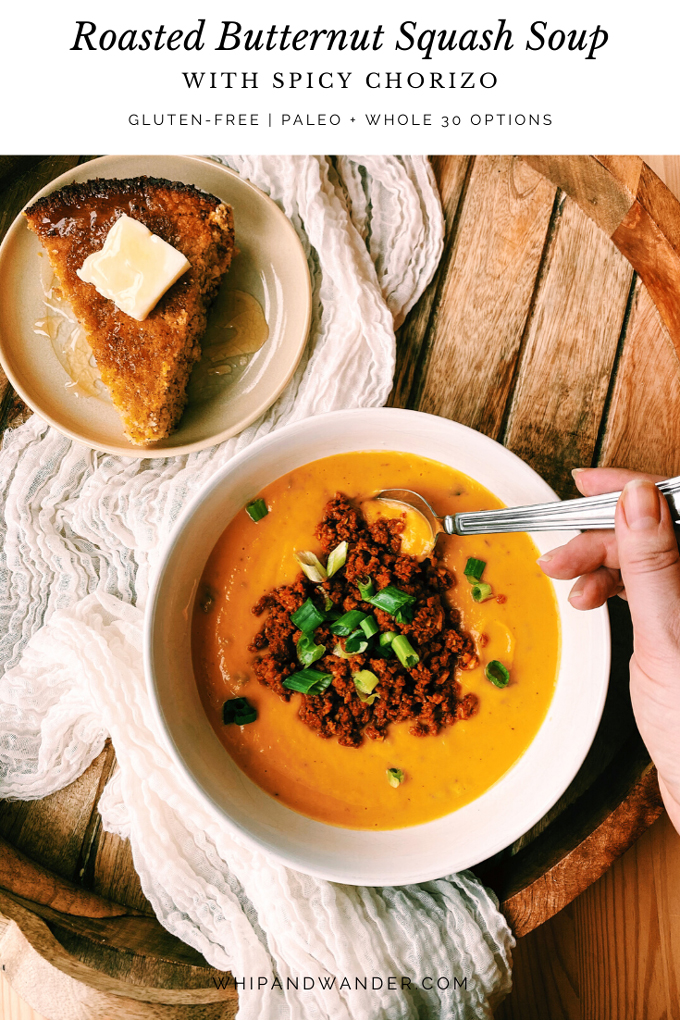 a hand with a spoon dipping into a bowl of chorizo topped Roasted Butternut Squash Soup with cornbread on a side plate resting nearby