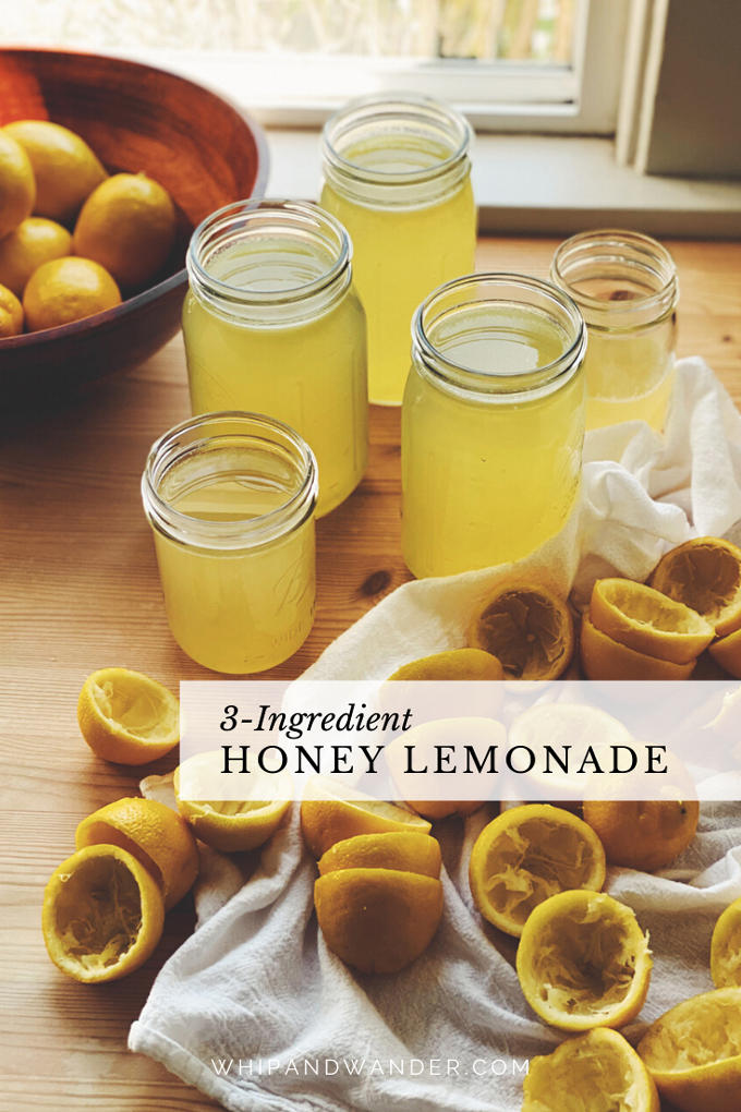honey lemonade in glass jars and a pile of squeezed lemons and a wood bowl filled with fresh lemons